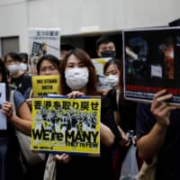 Protesters, including Hong Kongers living in Tokyo, hold banners at a rally in support of the pro-democracy movement in Hong Kong, near the city's economic and trade office in Tokyo last September. | REUTERS