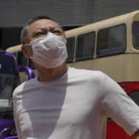 Occupy Central leader Benny Tai stands earlier this month in front of a vintage double-deck bus used as a polling center for an unofficial 'primary' for pro-democracy candidates ahead of legislative elections in Hong Kong.  | AP