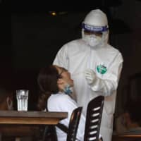 A health worker in Hanoi gets a test sample Wednesday from an employee at a pizza restaurant where another employee tested positive with the coronavirus after returning from Danang, Vietnam.  | REUTERS