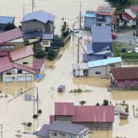 Houses are seen flooded in Okura, Yamagata Prefecture, Wednesday morning after the Mogami River began to overflow late Tuesday. | KYODO