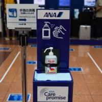 Hand sanitizer is placed in front of an All Nippon Airways check-in area at Haneda Airport in Tokyo. | BLOOMBERG