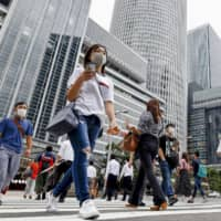 Pedestrians cross a street in Nagoya on Tuesday. Aichi Prefecture recorded 155 new COVID-19 cases Wednesday, according to NHK, a new single-day high for the prefecture.  | KYODO