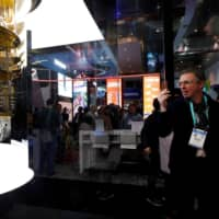 A man takes a photo of the IBM Q System One quantum computer during the 2020 CES in Las Vegas in January. | REUTERS
