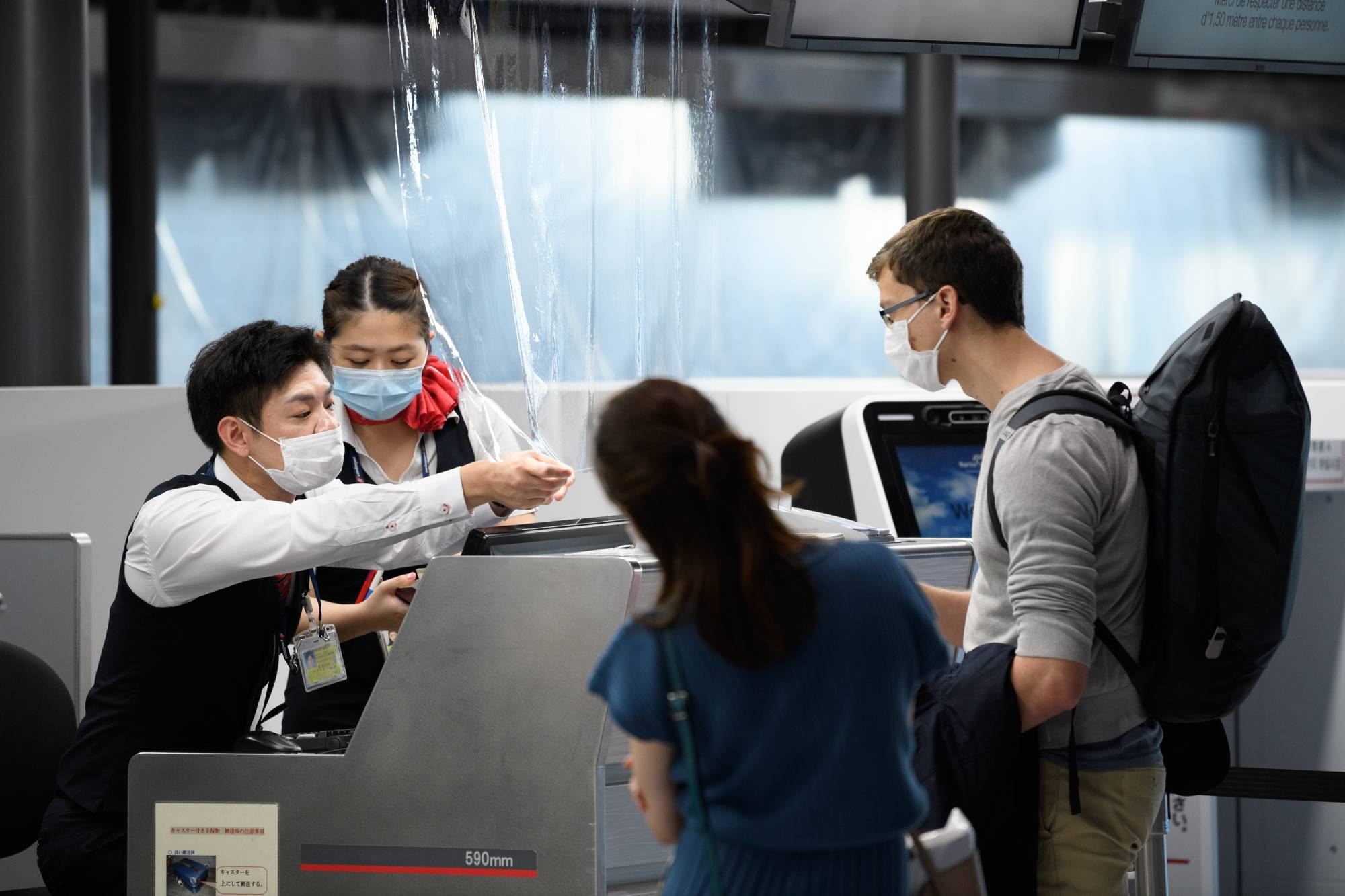 Employees assist passengers at the Air France-KLM Group check-in desk inside Narita Airport in Chiba Prefecture on July 19. | BLOOMBERG