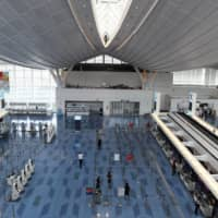 Workers stand in a check-in area at Haneda Airport in Tokyo on June 28. | BLOOMBERG