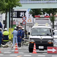 Police and firefighters examine the explosion site in Koriyama, Fukushima Prefecture, on Thursday.   KYODO