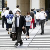 People walk in front of Tokyo Station on Tuesday. A panel of experts for the Cabinet Office said the country's economic expansion that began in December 2012 ended in October 2018, falling two months short of a record-long post-war growth period.   | KYODO