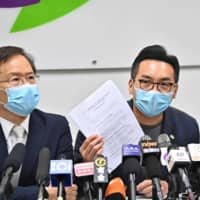 Civic Party leader Alvin Yeung (center) shows his disqualification notice during a news conference at the party's headquarters in Hong Kong on Thursday. A dozen local democracy activists, including Yeung, were disqualified from standing in the city's September legislative elections. | AFP-JIJI