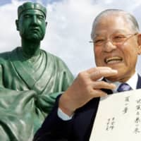 Former Taiwanese President Lee Teng-hui holds his own haiku poem in front of a statue of Matsuo Basho at the Basho Museum in Tokyo in 2007.  | AP