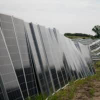 A worker unpacks solar panels at the Connexus Energy Athens Township solar-plus-storage project site in Athens Township, Minnesota. | BLOOMBERG