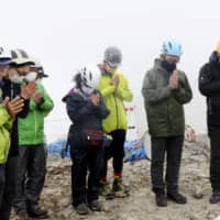 The kin of those killed in the September 2014 eruption of Mount Ontake offer prayers at Otaki Peak on Friday after entry restrictions were lifted for the first time since the disaster. | KYODO