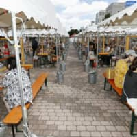 Visitors enjoy drinks Friday at the 'Mini Beer Garden' in Sapporo's Odori Park, with transparent acrylic boards set up between them to prevent coronavirus infections.  | KYODO