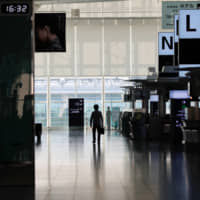 A person stands in an almost empty terminal of Tokyo's Haneda Airport in late April. Starting Tuesday, Japan is set to lift its entry restrictions on foreign residents, allowing those who left before the strict coronavirus curbs were imposed to return, and those planning to leave temporarily to proceed without fear of being locked out. | REUTERS
