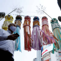 A man walks past Tanabata festival decorations that have letters saying 'stop the Coronavirus,' in Tokyo's Shibuya Ward on Monday. | REUTERS