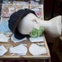 A mannequin head with a protective face mask and hat is displayed at a clothing store in Tokyo's Setagaya Ward on Sunday. | BLOOMBERG