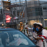 Staff hand over a concession box containing a face mask, hand sanitizer, and bag of popcorn to moviegoers at a Do it Theater's pop-up drive-in theater in Inzai, Chiba Prefecture, on Saturday. | BLOOMBERG