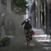 A pedestrian passes through a cooling mist spray in the Tokyo's Marunouchi district on Friday. | BLOOMBERG