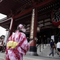 A visitor wearing a protective mask walks by Sensoji Temple in Tokyo's Asakusa district on Aug. 14. | AP