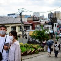 A couple wearing face masks take selfies at Yanaka Ginza shopping street in Tokyo on Aug. 1. | AFP-JIJI