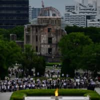 People gather in front of the ruins of the Hiroshima Prefectural Industrial Promotion Hall, now commonly known as the atomic bomb dome, during the 75th anniversary memorial service for atomic bomb victims at the Peace Memorial Park in Hiroshima on Aug. 6.