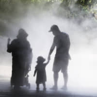 Visitors walk under a tunnel of mist to cool themselves in the searing heat at a zoo in Yokohama on Wednesday. | AP