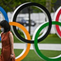 A woman wearing a face mask walks past the Olympic Rings installation in Tokyo on August 24. | AFP-JIJI