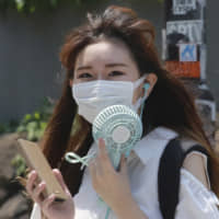 A woman wearing a face mask to help protect against the spread of the coronavirus holds a portable fan to avoid the heat in Tokyo on Wednesday. | REUTERS
