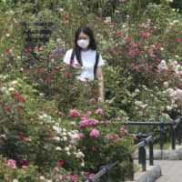 A woman wearing a face mask to protect against the spread of the new coronavirus visits a botanical garden in Tokyo on Monday. | AP