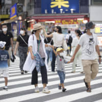 People wearing face masks walk across a traffic intersection in the Shinjuku district of Tokyo on Aug. 17. | AP