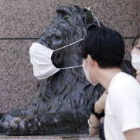 A landmark lion statue of a department store placed a protective mask is seen Aug. 12 in Tokyo. | AP