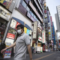 A man walks by restaurants in the Shinjuku district of Tokyo on Monday, Aug. 17, 2020. (AP Photo/Hiro Komae)