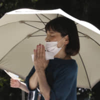 A woman wearing a face mask to protect against the spread of the new coronavirus prays at Kencho Temple in Kamakura, Kanagawa Prefecture, on Monday. | AP