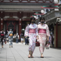 Two women in traditional kimonos wear face masks to help curb the spread of the coronavirus as they visit Sensoji Temple in Tokyo on Friday. | AP