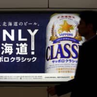 A man walks past an Sapporo Beer advertising board at New Chitose Airport Station in Hokkaido in 2016. | REUTERS