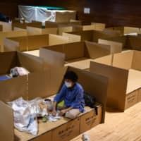 With torrential rain having battered parts of the nation during July, cardboard beds and partitions have become a staple at evacuation centers. | AFP-JIJI