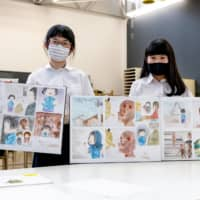 Mayuka Hirai (left) and Miyu Okazaki in Motomachi High School's A-bomb Drawing program display illustrations they're making to help younger children understand what happened in Hiroshima in 1945. | PETER CHORDAS