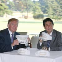 Slogan's heroes: U.S. President Donald Trump and Prime Minister Shinzo Abe show off hats adorned with the slogan 'Donald & Shinzo/Make Alliance Even Greater.' | KYODO