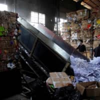 Laborers work at a paper products recycling station in Shanghai. | REUTERS