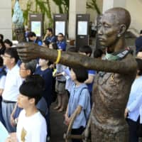 Civic group members in front of a museum in Busan, South Korea, on July 4, 2018, alongside a statue symbolizing Korean wartime laborers | KYODO