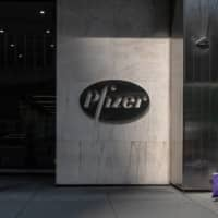 A pedestrian walks past Pfizer Inc. headquarters on July 22 in New York City. | GETTY IMAGES / VIA KYODO