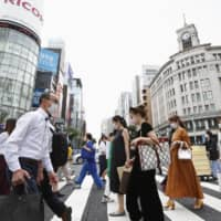 People stroll through Tokyo's glitzy Ginza shopping district on Thursday. | KYODO