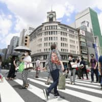 People walk with parasols in Tokyo's Ginza district on Saturday. | KYODO