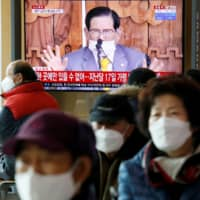 People watch a TV broadcasting a news report on a news conference held by Lee Man-hee, in Seoul in March.  | REUTERS