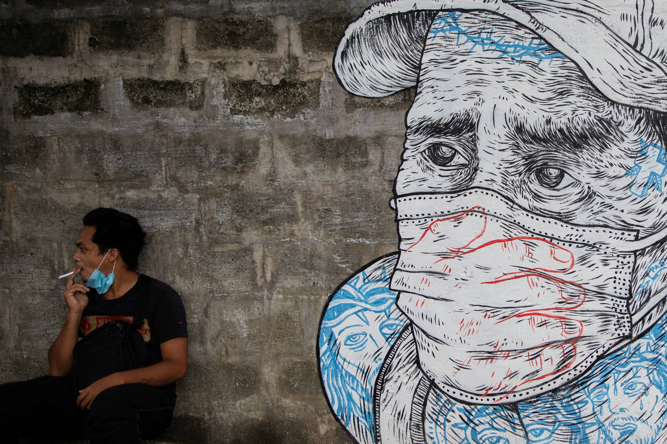 A man smokes a cigarette next to a mural in Manila on Thursday.  | REUTERS