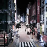 Pedestrians walk along a nearly empty street in Shinjuku.  | BLOOMBERG