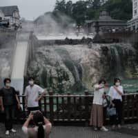 People pose in front of the source of a hot spring at Kusatsu Onsen in Kusatsu, Gunma Prefecture, on June 27. | BLOOMBERG