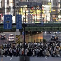 Pedestrians cross a road as dusk falls in Tokyo's Shinjuku district on July 10. | BLOOMBERG