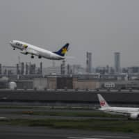 A Skymark jet takes off as a Japan Airlines plane taxis at Haneda Airport in Tokyo on June 28. | BLOOMBERG