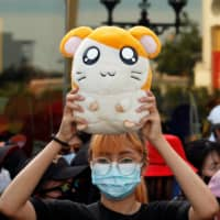 A demonstrator holds a stuffed Hamtaro toy  during a protest demanding the resignation of Thai Prime Minister Prayuth Chan-o-cha in Bangkok last month. | REUTERS