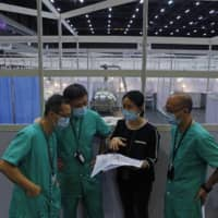 Medical workers prepare a temporary field hospital at Asia World Expo in Hong Kong on Saturday.  | AP